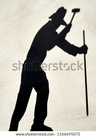 Shadow of a Person preparing to hammer a iron stake with a sledge hammer reflected on a cement slab