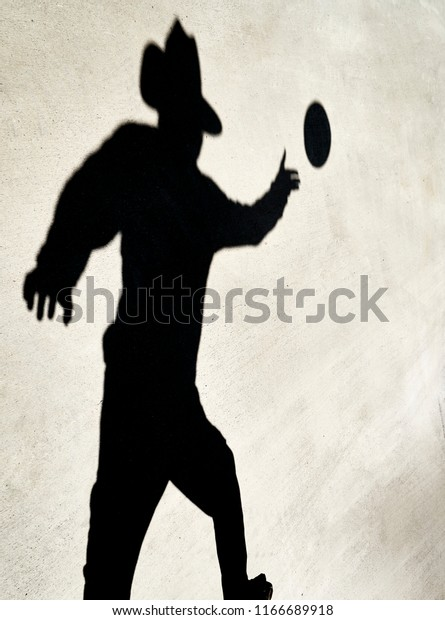 Shadow of a Person reaching to catch a disc reflected on a cement slab