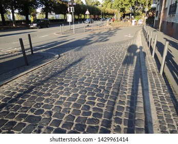 The shadow of the person reflected in the cobblestone
