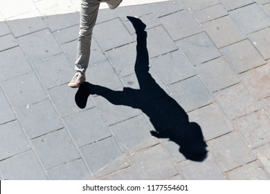 Shadow of a person running on the sidewalk