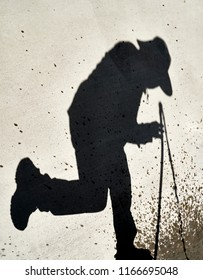 Shadow of a Person spraying a water hose reflected on a cement slab