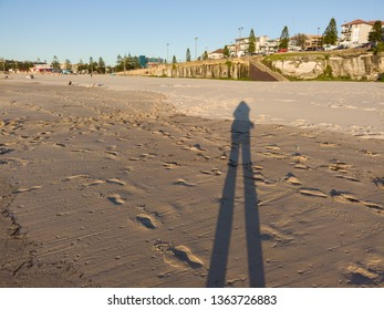 Shadow of a person standing in the sand.