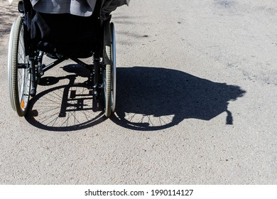 Shadow of a person in the wheelchair is shadowed to right. Shadow of a woman with a disability sitting on a wheelchair and the tires on asphalt. Shadow of the women sitting in wheelchair