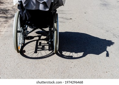 Shadow of a person in the wheelchair and the tires on asphalt. Shadow of a woman with a disability sitting on a wheelchair at midday. Women sitting in wheelchair is shadowed to right.