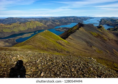 Langisjór with shadow of photographer at noon in good visibility all over Iceland highlands with Kerlingarfjöll on the left horizon and Tungaárjökull on the right and green and black hills in front