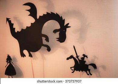 Shadow puppets of Dragon, Princess and Knight with soft glowing screen of shadow theater in the background