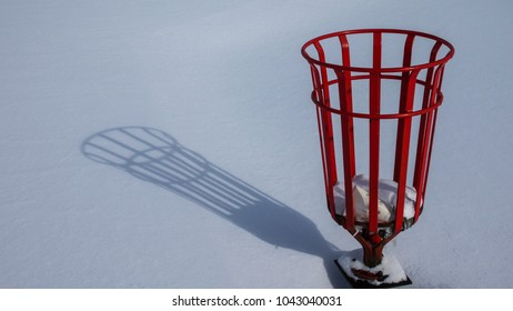 Shadow of a red metal litter bin on pristine snow.