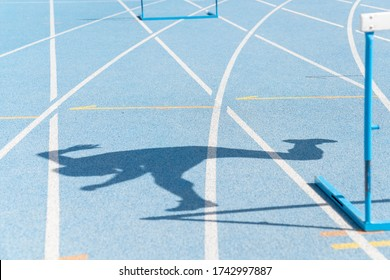 Shadow reflected on the floor of the running track of an obstacle career.