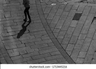 Shadow or silhouette of the legs of walking on the stone square man or woman. Strong sun light. Bright black white photo.