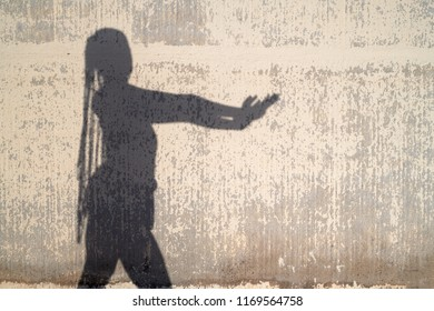Shadow silhouette of modern woman in dance against concrete wall insunlight