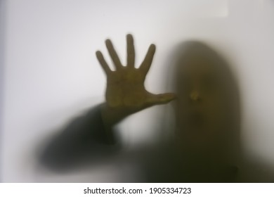 Shadow silhouette of person in glass, people behind mirror