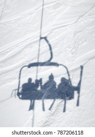 Shadow of skiers in ski lift chair, Val Thorens, France