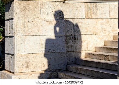 The shadow of Socrates statue outside Academy in Athens, Greece.