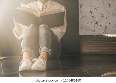 Shadow and soft focus,The girl sat on the floor in the corner to study the scriptures by reading alone and not wanting anyone to disturb in order to learn and understand the Bible to the fullest.