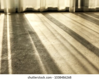 shadow of soft sunlight through fabric window blinds curtain on the floor empty room in door, evening sunshine feeling relax, warm, comfort like hometown, interior design idea, angle view from floor