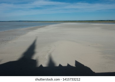 A shadow of the spire and ramparts of Le Mont St Michel is cast on the sandy tidal bay with a blue sky.copy space