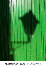 shadow of street lamp on green door