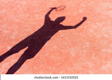 Shadow of successful man standing with arms raised on red tennis court during match