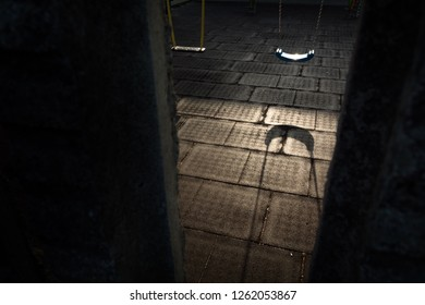 Shadow of a swing for children, in a dark playground. Sinister scene, where no person appears.