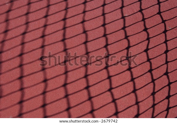 Shadow of a tennis net angled on a red court