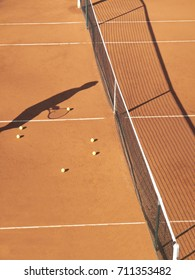 Shadow of tennis player at net with scattered tennis balls on clay court
