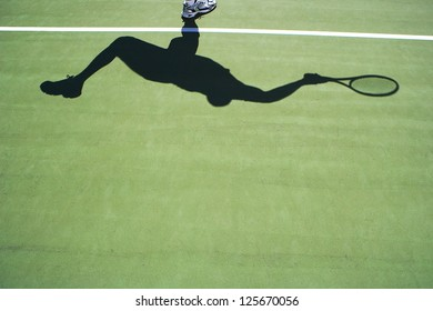 Shadow of tennis player on green tennis court
