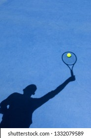 The shadow of a tennis player serving on a blue tennis court, with a tennis ball placed where it would be hit by the shadow of the racket; includes copy space for advertisement