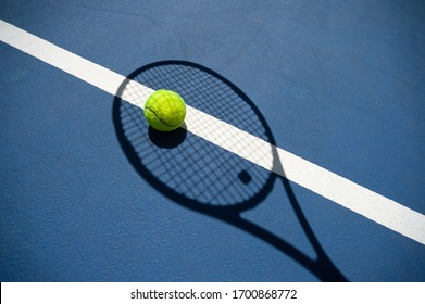 The shadow of the tennis racket and the tennis ball inside it. All on a blue tennis court.