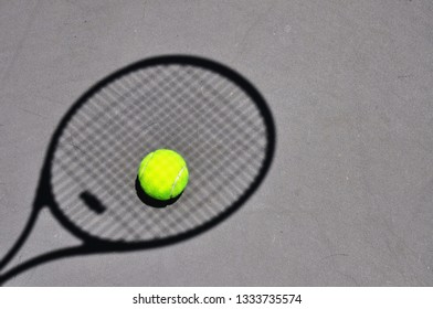 Shadow of a tennis racket with a tennis ball on the ground.
