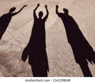 shadow of three people waving the middle person has both hands in the air the other two are waving with one hand. One person if wearing a cap and one is carrying a bag