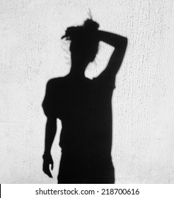 shadow of tired woman wiping forehead around on wall background
