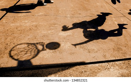 shadow of two basketball players on a playground
