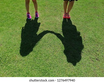 The shadow of two girls holding hands, On the green lawn in the daytime, concept of love, friendship, go together