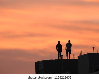 Shadow of two people with scattered sun light at twilight evening, on a Building top.