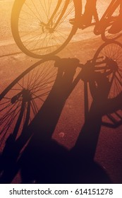 Shadow of unrecognizable cyclist riding a bike on road through city street in urban surrounding, retro toned