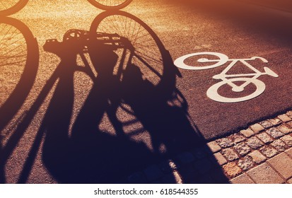 Shadow of unrecognizable cyclist riding a bike on bicycle lane through city street next to the road marking in urban surrounding, retro toned