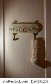 Shadow from a washcloth and BATHROOM signs on a wooden wall