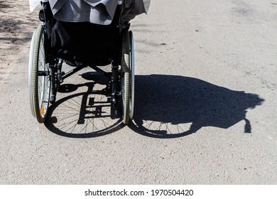 Shadow of the wheelchair and the tires. Shadow of a woman sitting on a wheelchair. Invisible women sitting in wheelchair is shadowed to right. Back of the wheelchair at outdoor shadowed to the right.