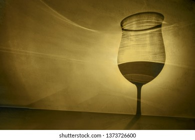 Shadow of wine glass in dark yellow light