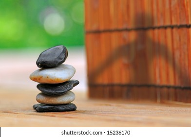 Shadow of woman doing yoga on fence by stacked smooth stones
