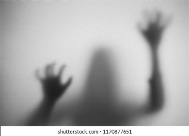 Shadow of woman on the frosted glass representing dangerous, fear, help, haunting, horror and scary.