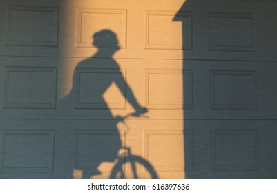 Shadow of a woman riding a bike on a textured wall. Two tonal image