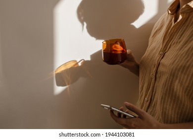 Shadow of woman in sunlit room and part body. Human wearing striped shirt holding cup with coffee and phone