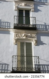 Shadow of wrought iron balcony railing.  Detail of old house facade, Segovia, Spain