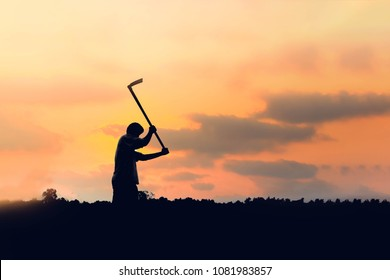 The shadow of a young man is shaking the soil with a spade in the evening.