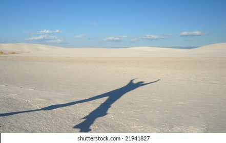 A shadow of a young woman jumping in the air on a white sand dune.