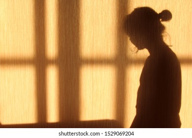 The shadow of a young woman shot against a yellow wall in profile