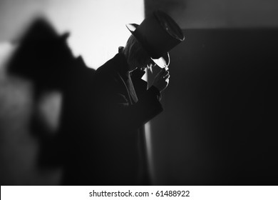 Shadowgraph of the man in black coat and hat standing near the wall and his shadow. Monochrome photo with natural darkness. Artistic grain added for movie effect