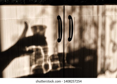 Shadows against the kitchen cabinet. Shadow hand on background kitchen. Cup and a decanter of water in the sun.