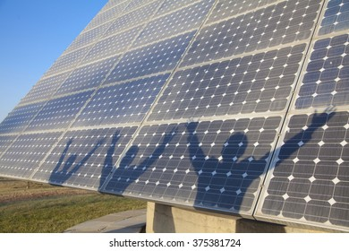 Shadows of Businesspeople with Arms Outstretched on Solar Panel
